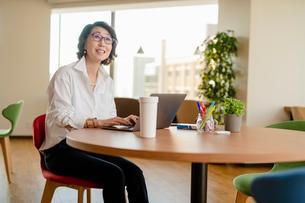 シェアオフィスでノートPCを操作する女性の写真素材 [FYI04098844]