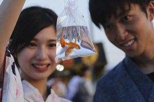 金魚を持つ浴衣姿のカップルの写真素材 [FYI04099104]