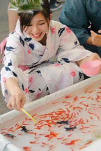 金魚すくいをする浴衣姿の女性の写真素材 [FYI04099106]