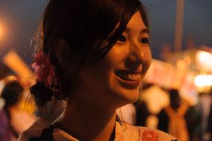お祭りで微笑む浴衣姿の女性の写真素材 [FYI04099119]