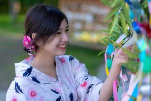七夕の飾りを見る浴衣姿の女性の写真素材 [FYI04099147]
