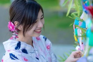 七夕の飾りを見る浴衣姿の女性の写真素材 [FYI04099148]