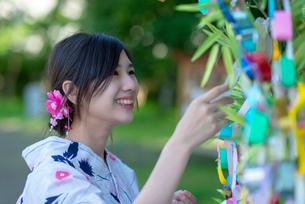 七夕の飾りを見る浴衣姿の女性の写真素材 [FYI04099149]