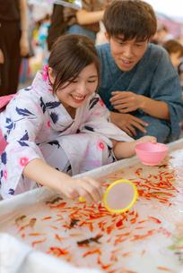 お祭りで金魚をすくう浴衣姿のカップルの写真素材 [FYI04099179]