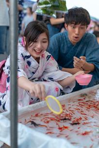お祭りで金魚をすくう浴衣姿のカップルの写真素材 [FYI04099181]