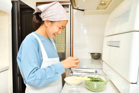 キッチンで料理をする女の子の写真素材 [FYI04100058]