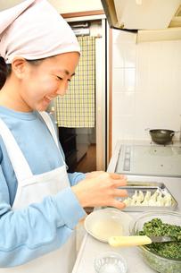 キッチンで料理をする女の子の写真素材 [FYI04100059]
