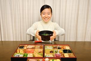 おせち料理を食べる女の子(正月)の写真素材 [FYI04100312]
