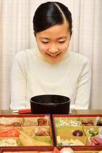 おせち料理を食べる女の子(正月)の写真素材 [FYI04100319]