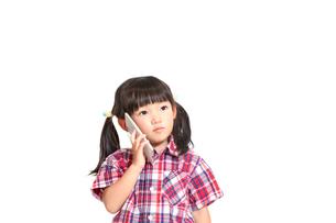 真剣な顔でスマートフォンで話をする幼い女の子。スマートフォン、相談、悩み、電話イメージの写真素材 [FYI04100355]