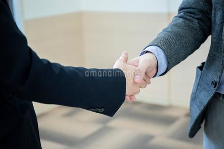 会議室で握手をするビジネスマンの手元の写真素材 [FYI04100492]