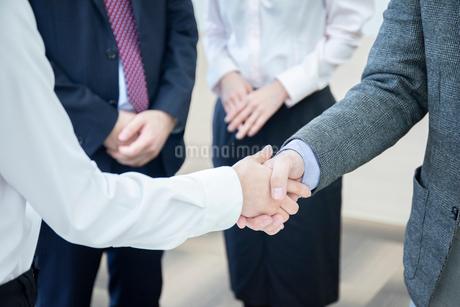 会議室で握手をするビジネスマンの手元の写真素材 [FYI04100495]