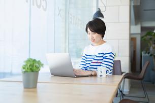 シェアオフィスでノートPCを操作する女性の写真素材 [FYI04100861]