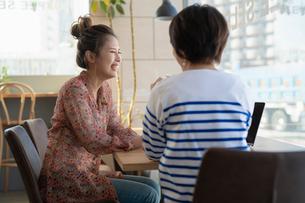 ノートPCを見ながら談笑する女性2人の写真素材 [FYI04100878]