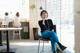 窓際でスマホで通話する女性の写真素材 [FYI04100883]