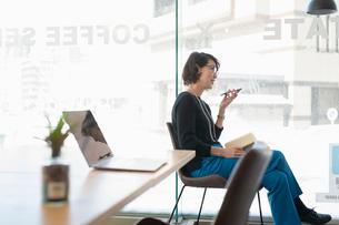 シェアオフィスでスマホでスピーカー通話する女性の写真素材 [FYI04100891]