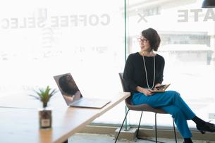 シェアオフィスで後ろを振り返る笑顔の女性の写真素材 [FYI04100901]