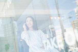 窓際でスマホで通話する女性の写真素材 [FYI04100907]