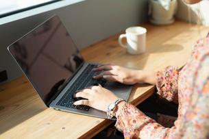 シェアオフィスでノートPCを操作する女性の手元の写真素材 [FYI04100911]