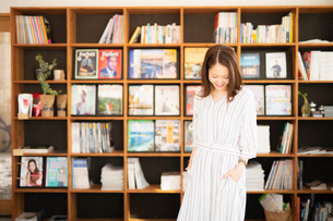 本棚の前の女性の写真素材 [FYI04100986]
