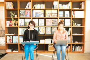 本を読む女性とノートPCを操作する女性の写真素材 [FYI04100997]