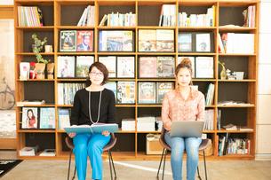 本を読む女性とノートPCを操作する女性の写真素材 [FYI04101000]