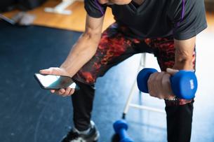 ヘルスケアアプリでチェックしながらダンベル運動をする男性の写真素材 [FYI04101043]