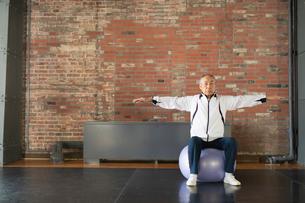 バランスボールで体幹トレーニングするシニアの男性の写真素材 [FYI04101045]