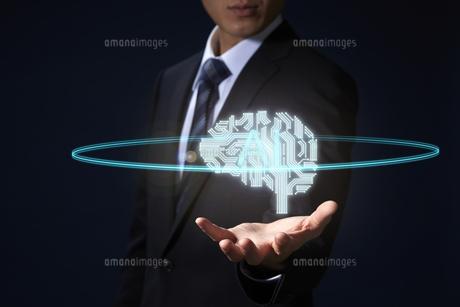 男性の手から浮かび上がるCGの脳のイラストとAIの文字の写真素材 [FYI04101124]