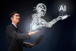 パソコンを持った男性と光線で描かれたロボットのCGの写真素材 [FYI04101125]