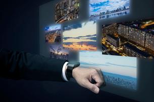 スマートウォッチで様々な景色を映し出すサラリーマンの手元の写真素材 [FYI04101131]