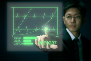 ホログラムで心電図を調べるサラリーマンの写真素材 [FYI04101135]
