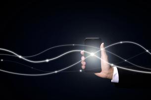 スマートフォンとネットワークを繋ぐ光の写真素材 [FYI04101137]