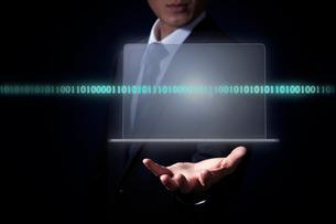 スーツ姿の男性の手から浮かび上がるノートパソコンとC言語の写真素材 [FYI04101146]