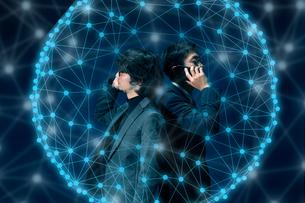 スマートフォンで通話する男性2人と青く発光する点と線の球体の写真素材 [FYI04101149]