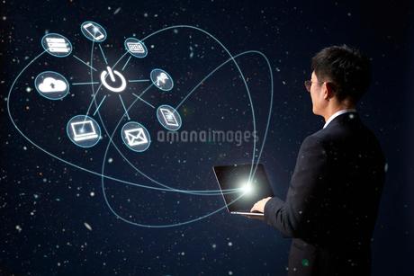 アイコンが飛び出したパソコンを操作しているスーツの男性の写真素材 [FYI04101310]