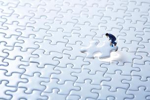 一面の白いパズルと1ピースをはめるミニチュア人形の写真素材 [FYI04101372]