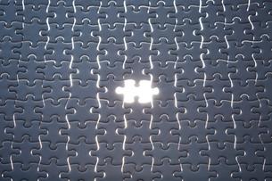 暗闇の一面の白いパズルと光る1ピースの写真素材 [FYI04101373]