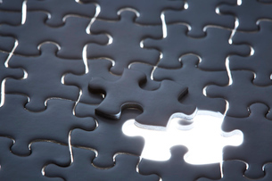 暗闇の白いパズルと光る1ピースの写真素材 [FYI04101375]