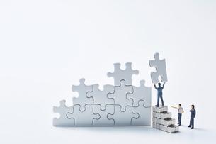 白いパズルを組み立てる3体のミニチュア人形の写真素材 [FYI04101380]