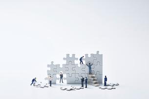 白いパズルを組み立てる複数のミニチュア人形の写真素材 [FYI04101382]