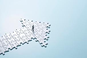 水色の背景と白いパズルの矢印と歩くミニチュア人形の写真素材 [FYI04101393]
