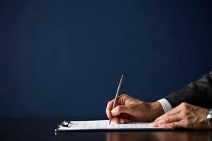 書類にボールペンで記入するサラリーマンの写真素材 [FYI04101418]