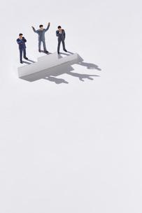 表彰台に登るスーツ姿のミニチュアたちの写真素材 [FYI04101443]