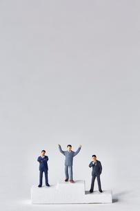 表彰台に登るスーツ姿のミニチュアたちの写真素材 [FYI04101446]
