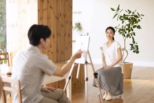 室内で女性モデルのスケッチをする男性の写真素材 [FYI04102294]