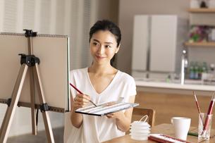 室内で筆を持ち絵を描く女性の写真素材 [FYI04102296]