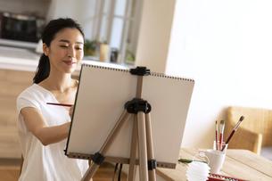 室内で筆を持ち絵を描く女性の写真素材 [FYI04102297]