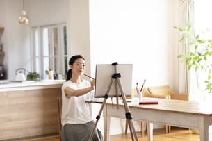 室内で筆を持ち絵を描く女性の写真素材 [FYI04102299]