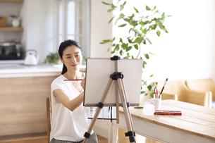 室内で筆を持ち絵を描く女性の写真素材 [FYI04102300]